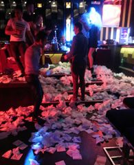 Napkins shower over revellers and cover the floor like snow