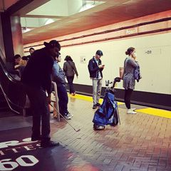 Guy playing golf in the subway station